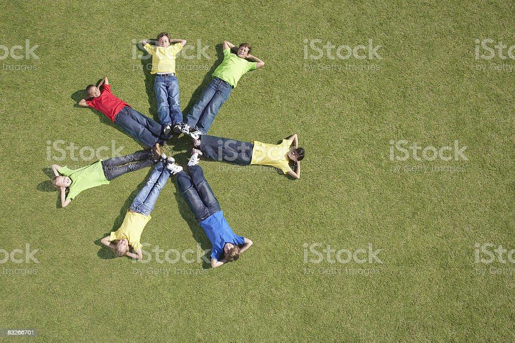 Gruppe von Kindern Leg dich auf Gras im Kreis formation Lizenzfreies stock-foto