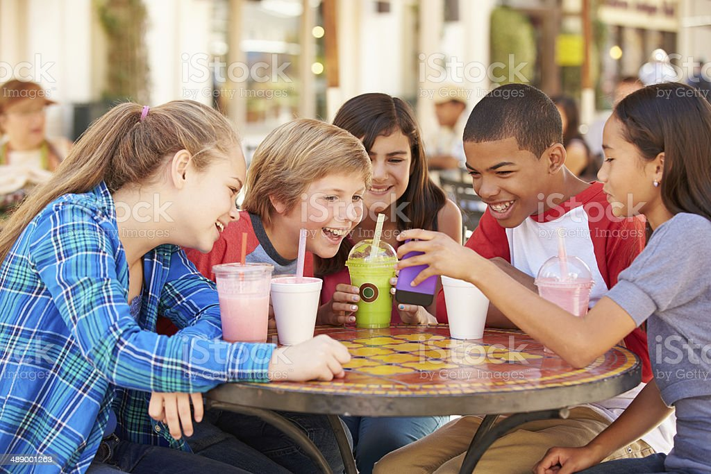 Group Of Children  Looking At Text On Mobile Phone stock photo