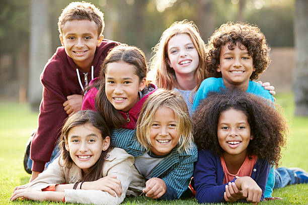 gruppe von kindern liegen zusammen auf gras im park - kind vor der pubertät stock-fotos und bilder