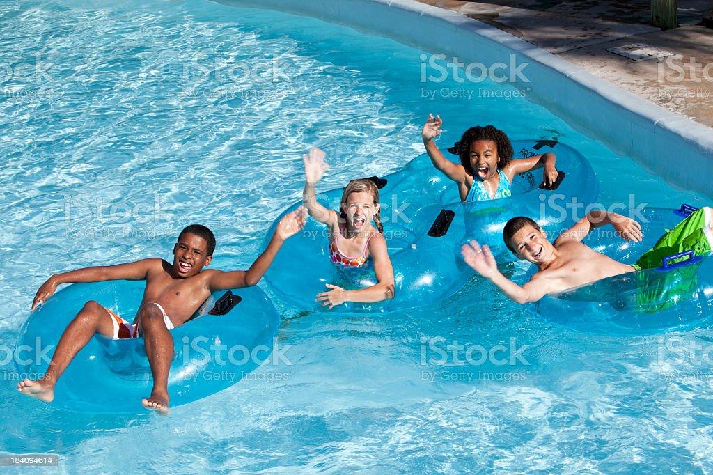 Group of children on innertubes at water park stock photo