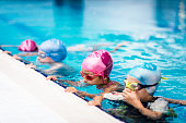 Group of children on swimming class, making bubbles