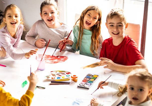 Group of children painting with water colors together stock photo