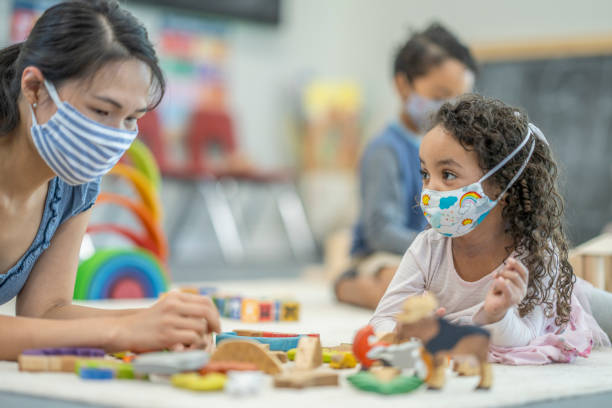 Group of children playing at daycare while wearing protective face masks stock photo