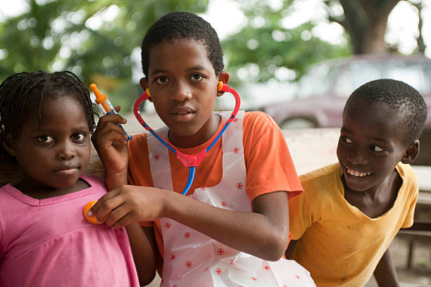 Group of children playing doctor Leogane, Haiti - June 28, 2011: Group of  children playing doctor. The boy is listening with a stethoscope to the heartbeat of a younger girl. haitian ethnicity stock pictures, royalty-free photos & images