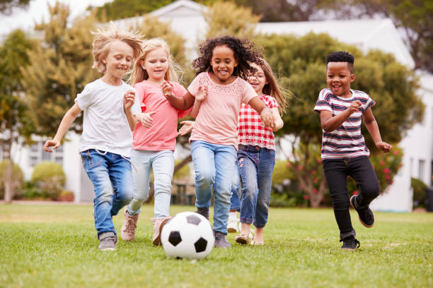 group of children playing football with friends in park - ambientazione esterna foto e immagini stock