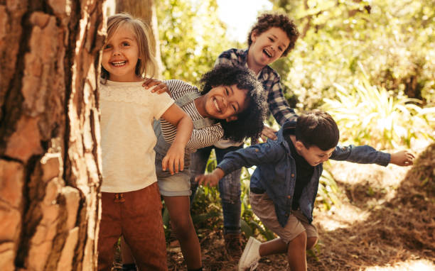 Group of children playing hide and seek Cute smiling kids peeking out from behind the tree in the park. Group of children enjoying playing hide and seek in a forest. children only stock pictures, royalty-free photos & images