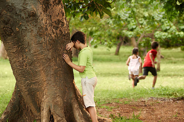 group of children playing hide and seek young boys and girls playing hide and seek in park, with kid counting leaning on tree hide and seek stock pictures, royalty-free photos & images
