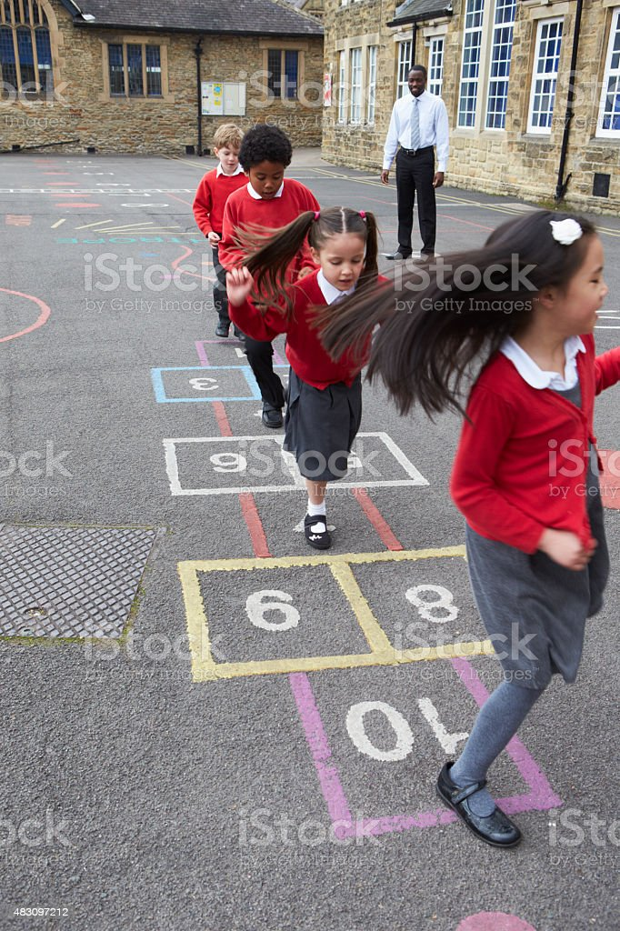 Group Of Children Playing Hopscotch In School Playground stock photo