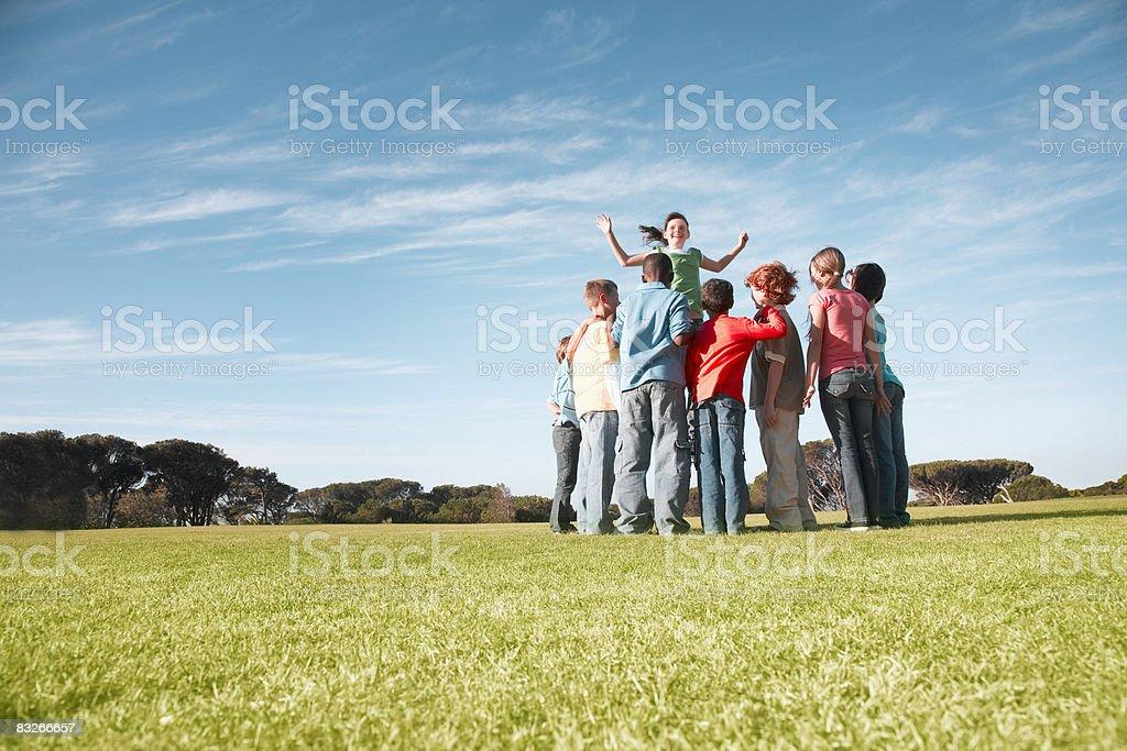 Group of children playing in park royaltyfri bildbanksbilder