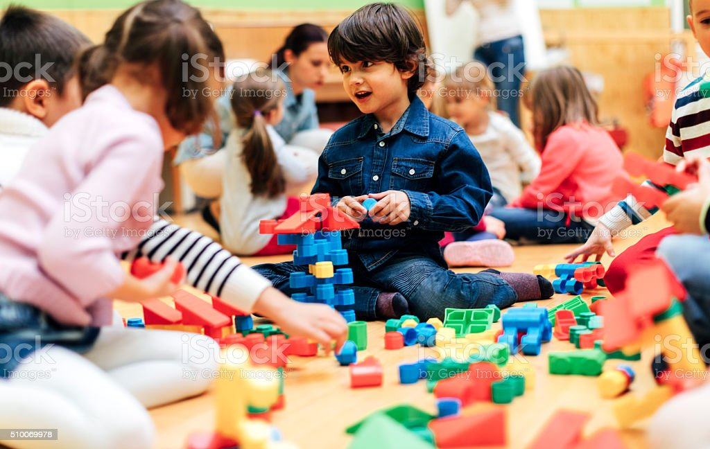 Group of children playing with blocks in kindergarten. stock photo
