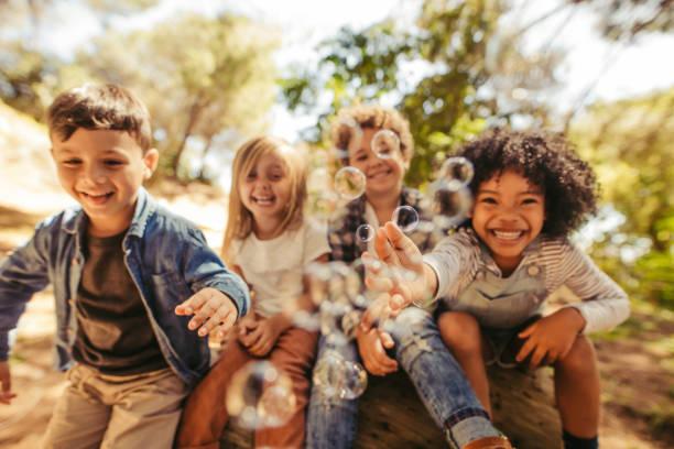 gruppo di bambini che giocano con bolle di sapone - bambino foto e immagini stock
