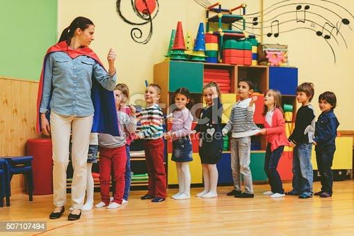 istock Group of children playing with their teacher in kindergarten 507107494