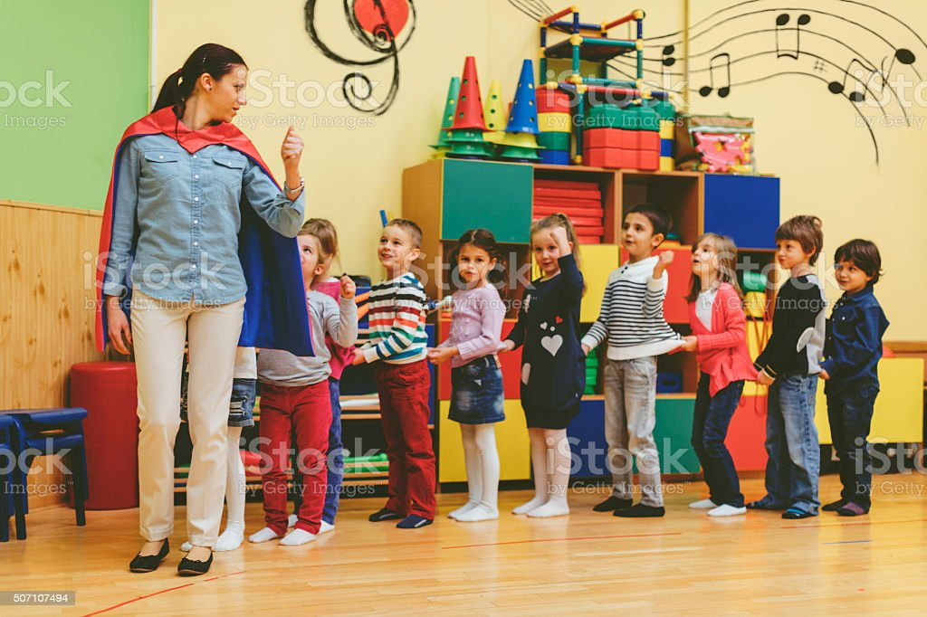 Group of children playing with their teacher in kindergarten stock photo