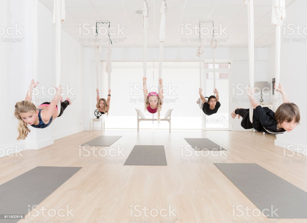 Group of children practicing aerial yoga stock photo