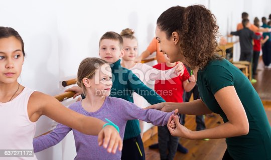 istock Group of children practicing at the ballet barre 637271172