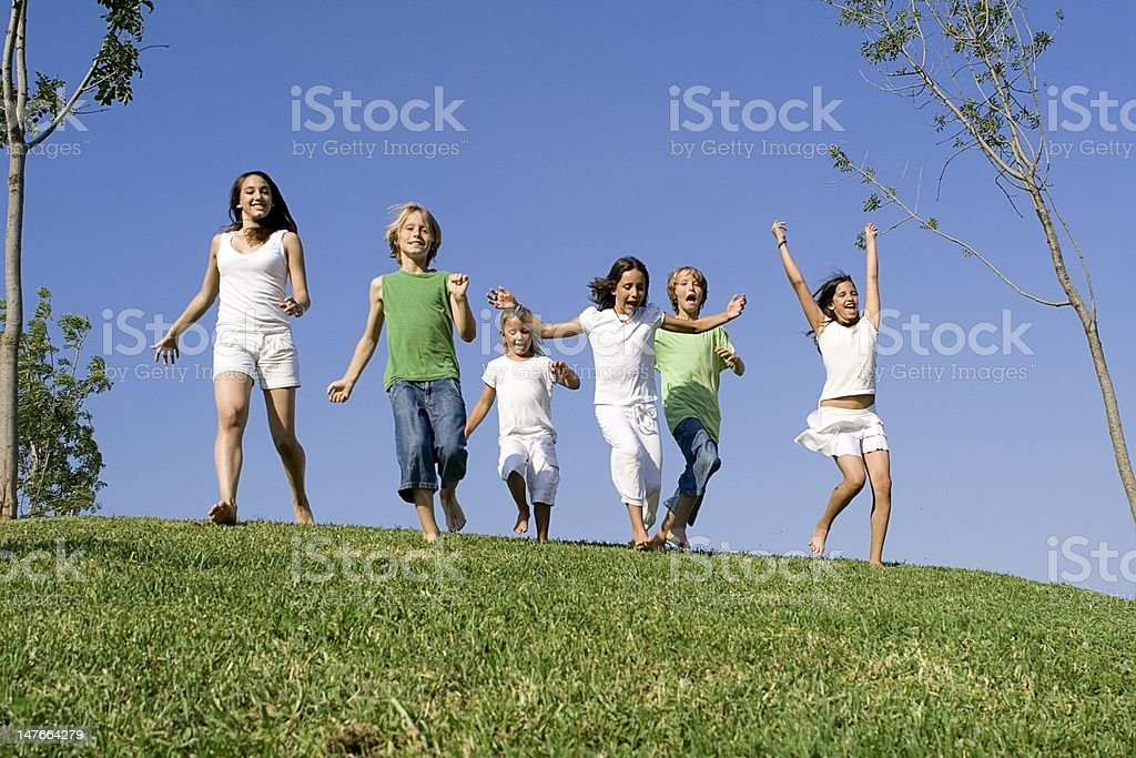 group of children running over hilltop royalty-free stock photo