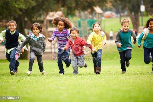 istock Group of children running over playground grass 494396147