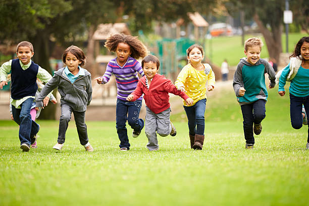 Group of children running over playground grass stock photo