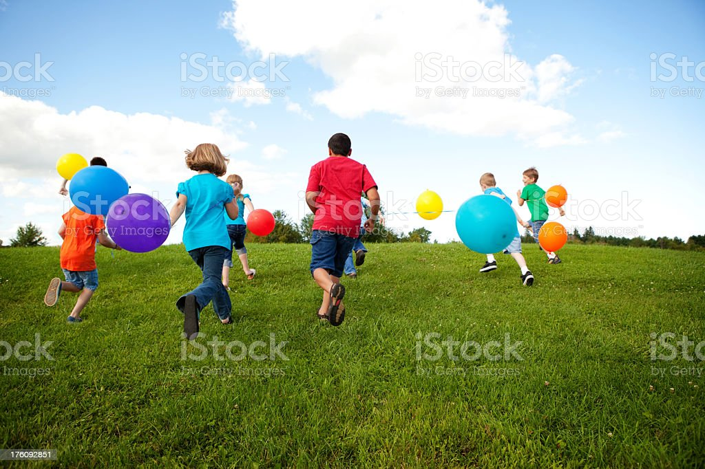 Group of Children Running with Balloons Outside royalty-free stock photo