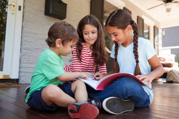 Group Of Children Sit On Porch Of House Reading Books Together Group Of Children Sit On Porch Of House Reading Books Together sibling stock pictures, royalty-free photos & images