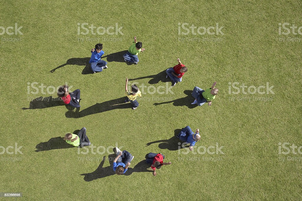 Group of children sitting in a circle playing royalty-free stock photo