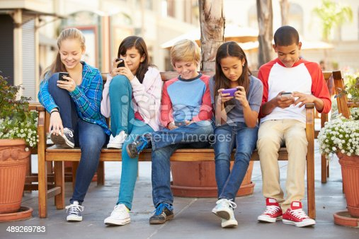 istock Group Of Children Sitting In Mall Using Mobile Phones 489269783