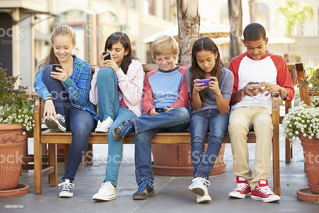 Group Of Children Sitting In Mall Using Mobile Phones stock photo