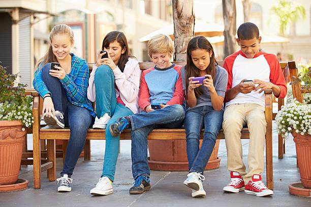 gruppe von kindern sitting in mall mit handy - kind vor der pubertät stock-fotos und bilder