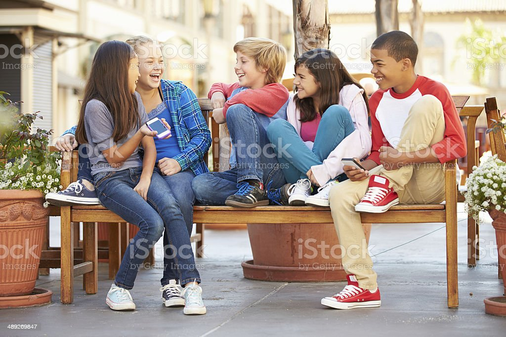Group Of Children Sitting On Bench In Mall royalty-free stock photo
