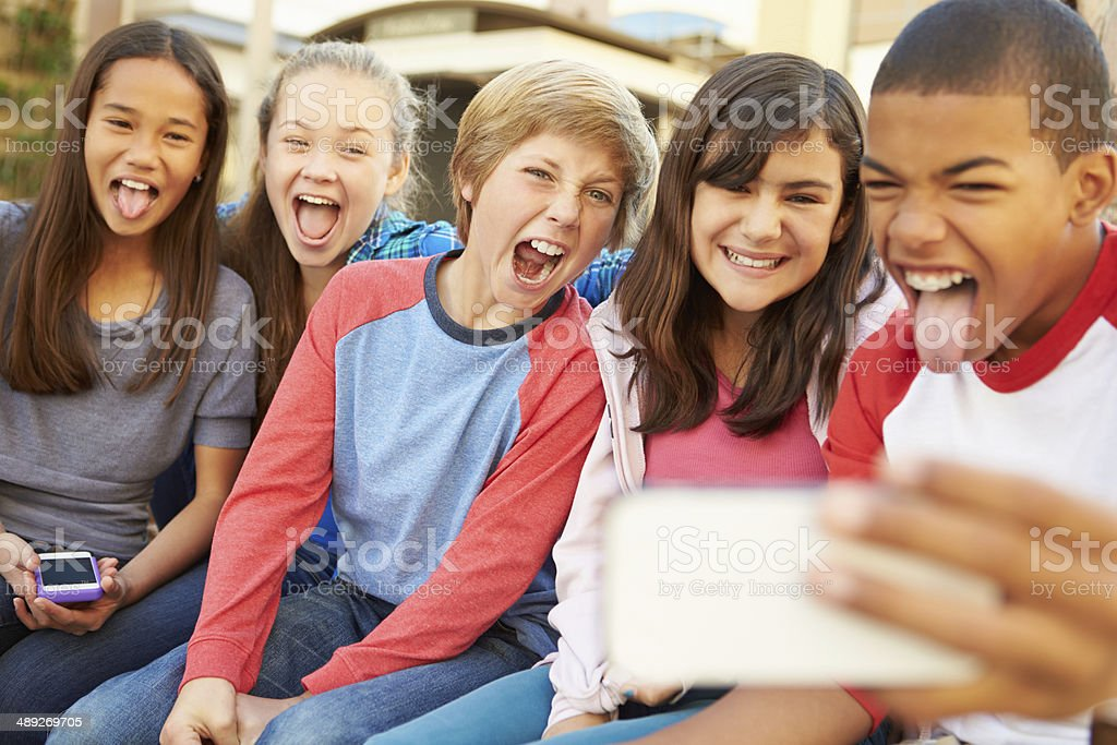 Group Of Children Sitting On Bench In Mall Taking Selfie stock photo