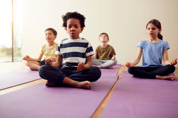Group Of Children Sitting On Exercise Mats And Meditating In Yoga Studio stock photo