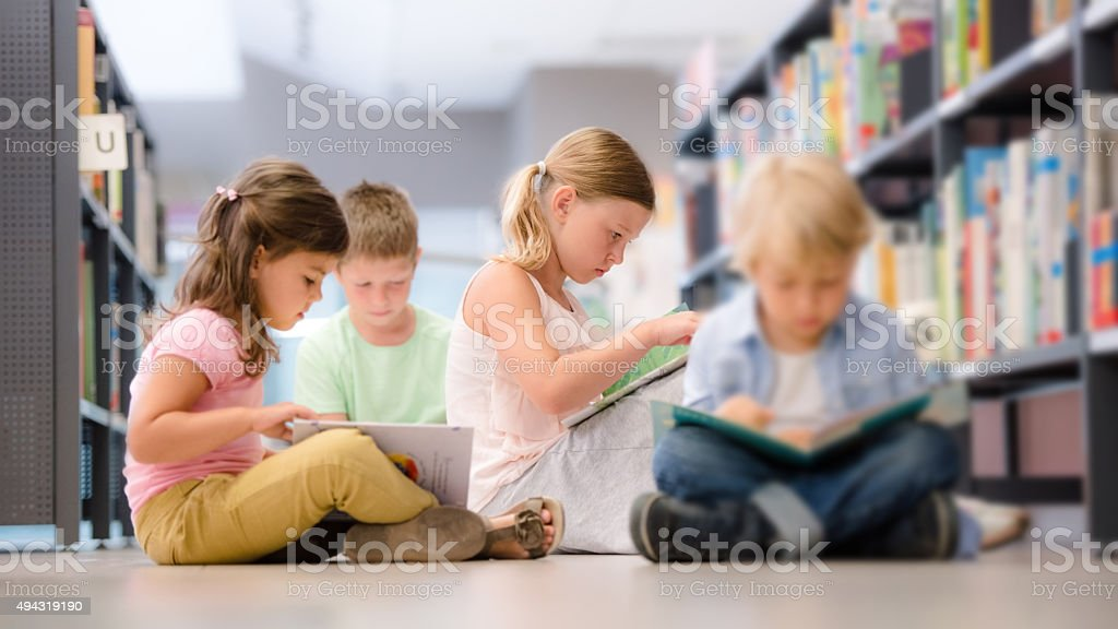 Group of children sitting on floor and reading stock photo