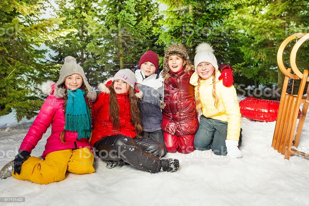 Group of children sitting on snow in winter time stock photo