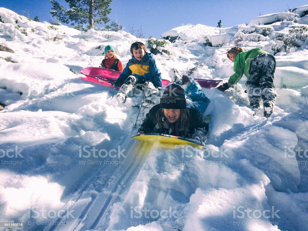 Group of children sledding together stock photo