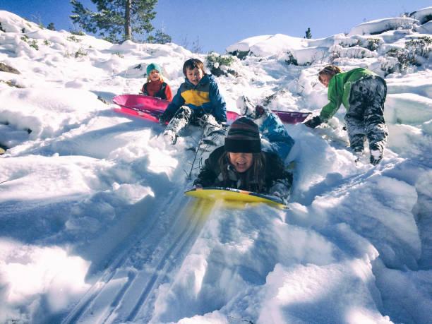 group of children sledding together - all vocabulary zdjęcia i obrazy z banku zdjęć