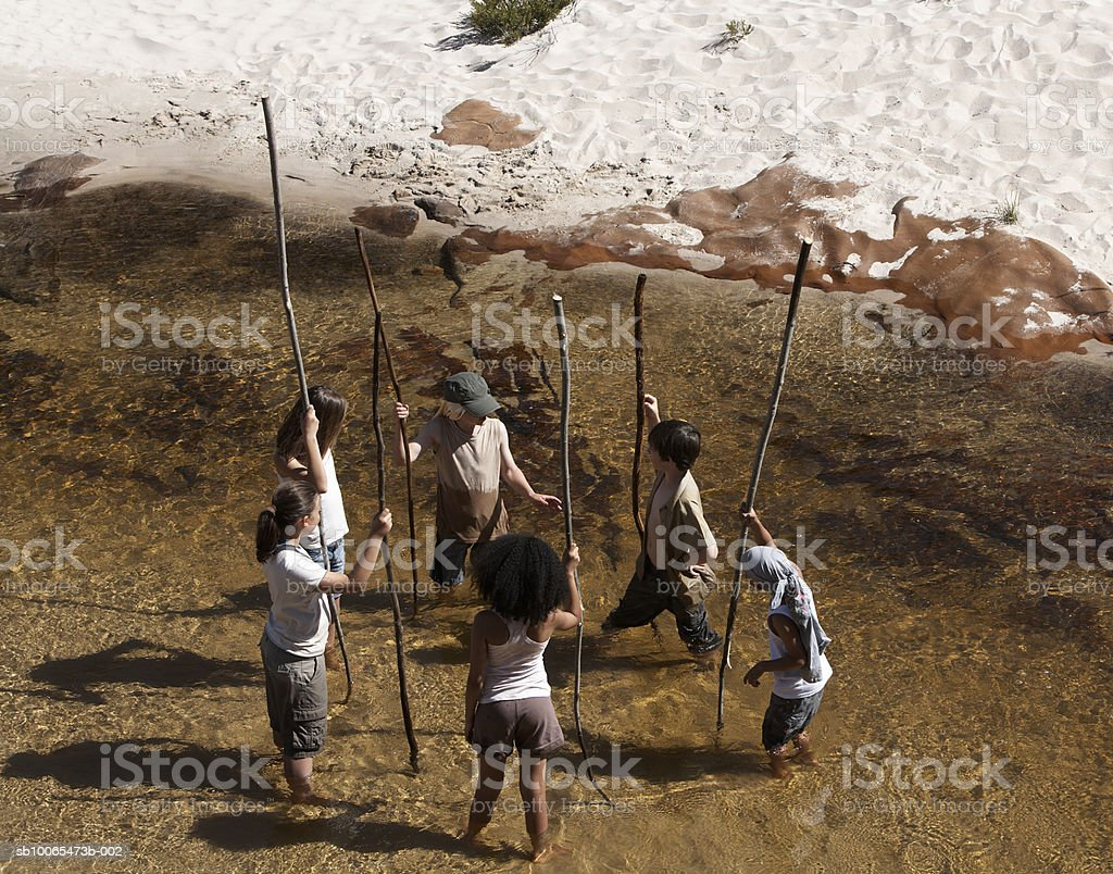 Group of children (6-13) standing in stream with holding pole royalty-free stock photo