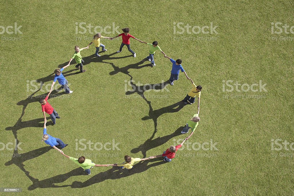Group of children walking in circle holding hands stock photo