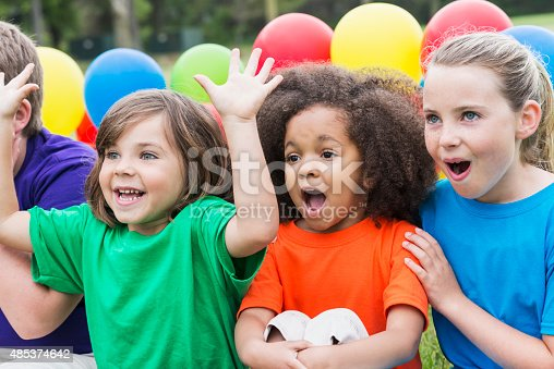 A group of multi-ethnic children, ages 5 to 10, sitting together in a row, in colorful shirts, in front of colorful balloons, watching something amazing.