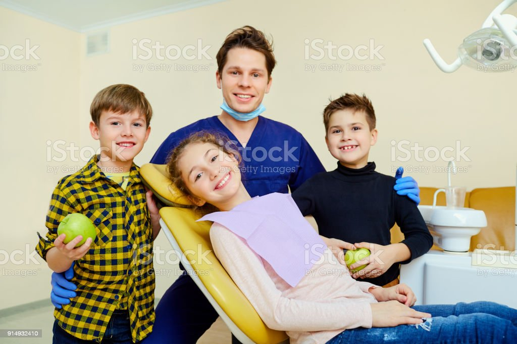 A group of children with a dentist a man smiling stock photo