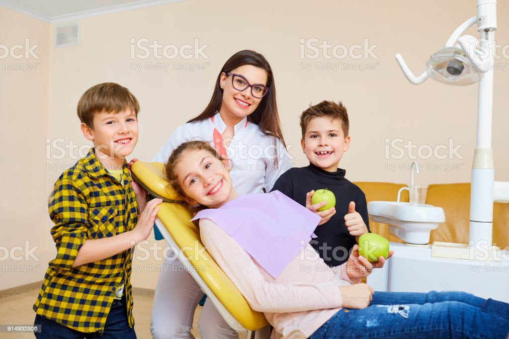 A group of children with a dentist a woman smiling stock photo