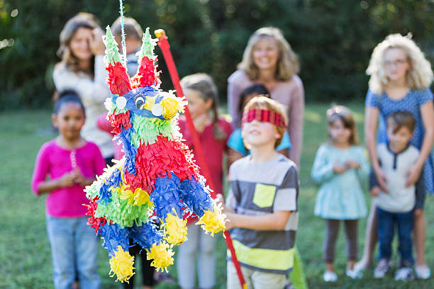 group of children with boy hitting pinata - cinco de mayo party stock photos and pictures