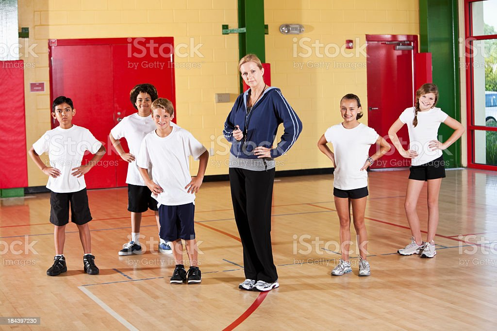 Group of children with coach in school gym royalty-free stock photo
