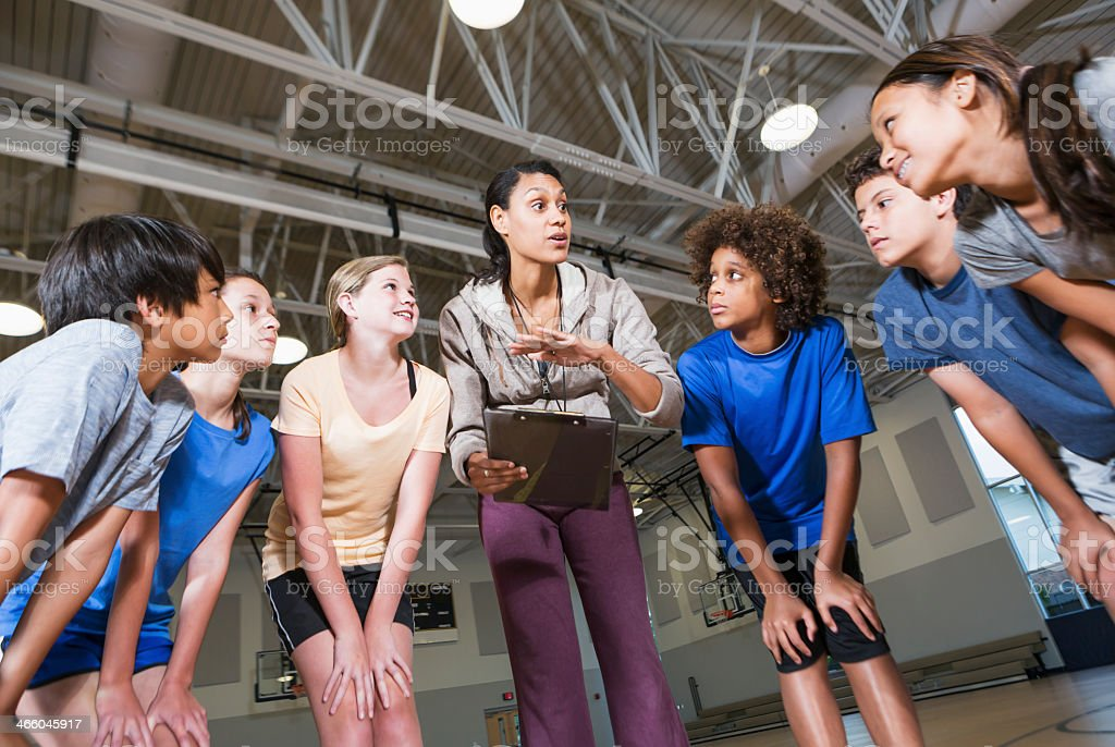 Group of children with coach in school gym stock photo