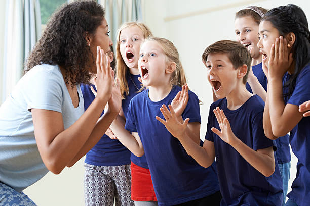 group of children with teacher enjoying drama class together - middle school teacher stock pictures, royalty-free photos & images