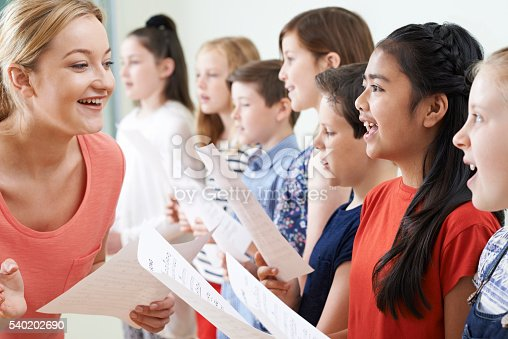 1155122702 istock photo Group Of Children With Teacher Enjoying Singing Group 540202690