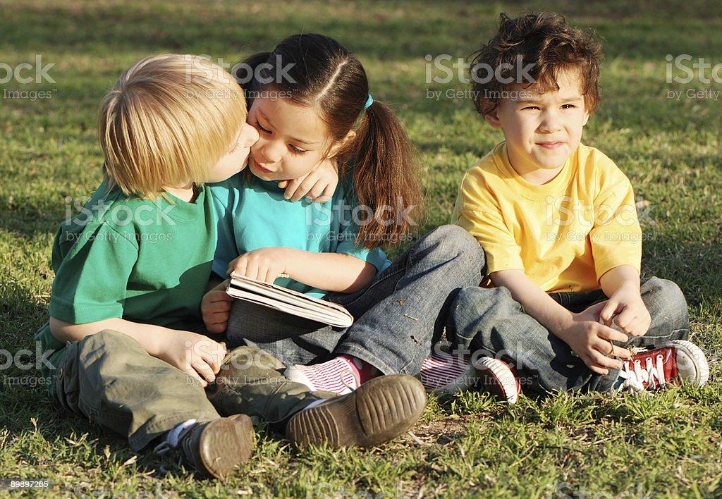 Groupe d'enfants avec le livre sur une herbe photo libre de droits