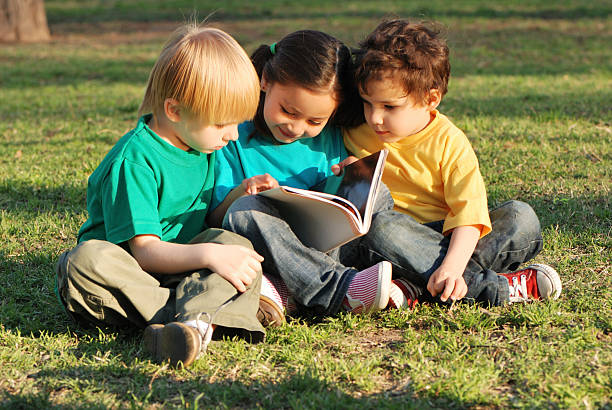 Group of children with the book on a grass stock photo