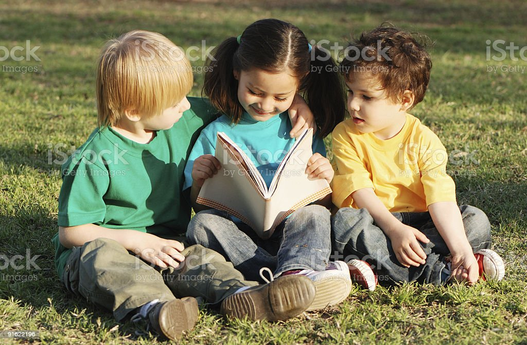 Group of children with the book on a grass royalty-free stock photo
