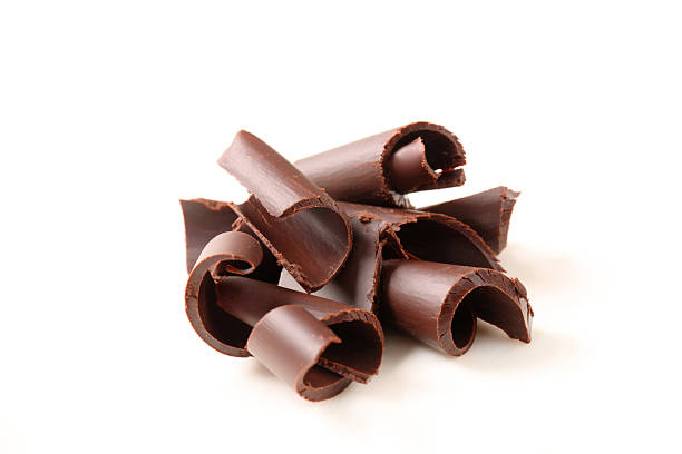 group of chocolate curls on a white background - chocolate swirl stock photos and pictures