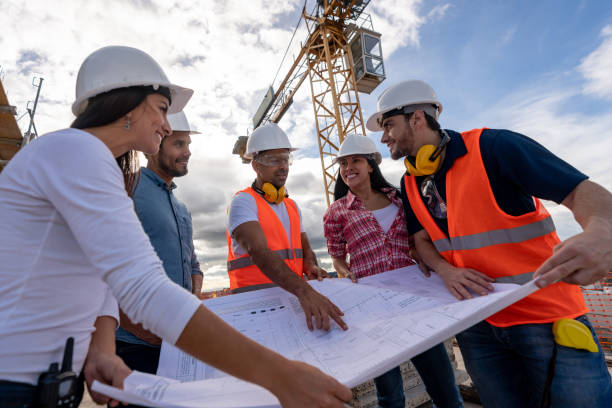 group of civil engineers looking at a blueprint at a construction site - civil engineer stock photos and pictures